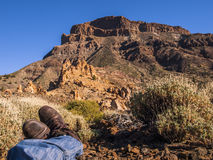 Lying in the bushes. Men lying down on the ground - picture taking over his jeans and boots - volcanic landscape - stone - sand - hills - blue sky - bright Royalty Free Stock Photos