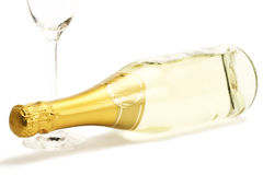 Lying champagne bottle with a empty champagne glas Stock Image