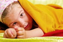 Lying child. Child lying in colored textiles fabric Stock Image