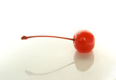 Lying cocktail cherry. Red compoted cocktail cherry lying on the white background Royalty Free Stock Photo