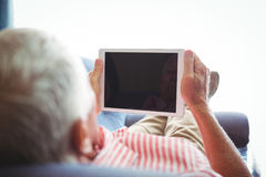 Lying on a couch senior man looking at digital tablet Stock Photo