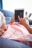 Lying on a couch senior man touching digital tablet. On a sunny day Stock Photography