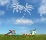 Lying couple on grass and dream island collage royalty free stock photo