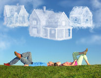 Lying couple on grass and dream three cloud houses stock photography