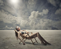 Lying in the desert. A young girl is lying in a chair while wearing sunglasses and a swimsuit; the desert in the background Royalty Free Stock Photography