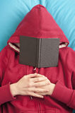 Lying down with book covering face Royalty Free Stock Images