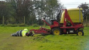 Lying down on the job. Workman fixing a grass cutter Stock Image