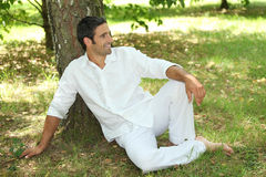 Lying down under a tree. 35 years old lying down under a tree Royalty Free Stock Image
