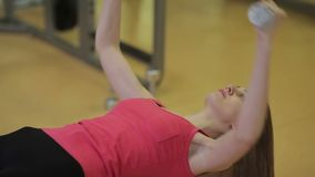 Lying dumbbell bench press. Girl performing lying dumbbell bench press. Personal trainer assisting woman in gym stock video