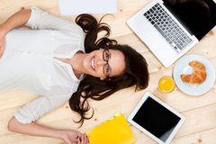 Lying female. With laptop, digital tablet and food on the floor Stock Image