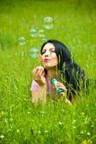Lying in field and blowing soap bubbles Stock Photo