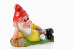 Lying garden gnome holding flower Stock Images