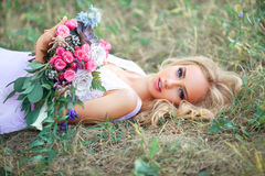 Lying girl with a bouquet Stock Photos