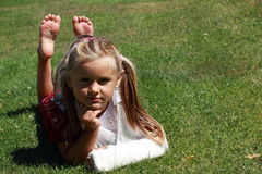 Lying girl with broken hand. Barefoot girl in red dress with broken hand lying on the grass Stock Images