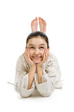 The lying girl does by feet over a head. The lying girl in a sports kimono does by feet ears of a rabbit Royalty Free Stock Photography