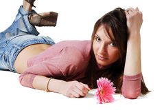 Lying girl with a flower. In her hand isolated on white background Stock Photography