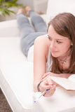 Lying girl studying on a sofa Royalty Free Stock Photos