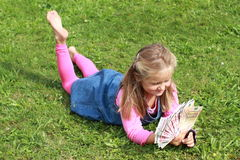 Lying girl watching money. Basrefoot girl in blue dress lying on the grass watching lots of euros royalty free stock photo