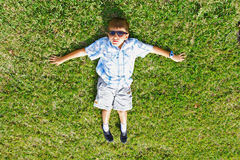 Lying on the Grass. Little kid lying on the grass wearing sunglasses. Abstract Angle Royalty Free Stock Image
