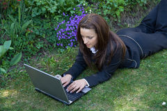 Lying in grass with laptop Stock Photo