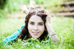 Lying on grass pretty smiling girl Stock Images