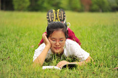 Lying on grass and reading Stock Images