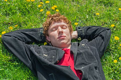 Lying on grass. Young guy lying on the field with dandelions eyes closed Stock Photos