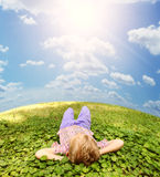 Lying on green grass carefree boy. Carefree little boy lying on the green grass under blue sky Royalty Free Stock Photography
