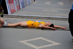 Lying on the ground of the runner. A crossed the finish line is too tired to lie on the ground of the runner.Half international marathon in fushui county in Royalty Free Stock Photo