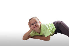 Lying horizontally girl with glasses in gray jeans. On white background Royalty Free Stock Image