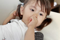 Lying Japanese girl with sucking her finger Stock Photography