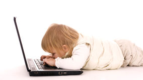 Lying little baby writing on the laptop Stock Photos