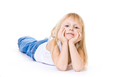 Lying little girl in white top and blue jeans Royalty Free Stock Images