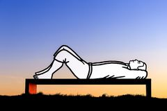 Lying man on a bench at sunset Stock Photos
