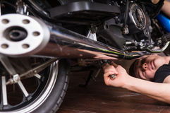 Lying Man Fixing his Motorbike Using Wrench Tool Royalty Free Stock Image