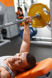 Lying man lifting barbell in gym Royalty Free Stock Photos