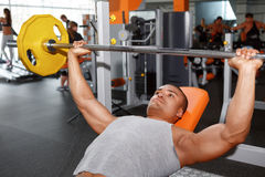 Lying man lifting barbell in gym Stock Image