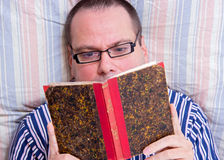 Lying man reading a book Stock Photo