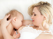 Lying mother breast feeding her child. Mother breast feeding her child Royalty Free Stock Image