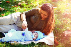 Lying mother and her baby outside the nature Stock Photos