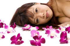 Lying With Orchids. A young Asian woman lying on the floor with purple orchid flowers Royalty Free Stock Images