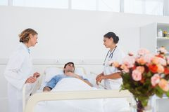Lying patient in his bed looking to his doctors Stock Image
