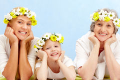 Lying people. Portrait of grandmother, mother, grandchild with diadems lying in the studio Royalty Free Stock Photography