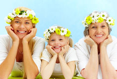 Lying people. Portrait of grandmother, mother, grandchild with diadems lying in the studio Royalty Free Stock Images
