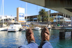 Pier relaxing. Lying on the pier stretching legs in boots and admiring the yachts in Barselona Stock Images