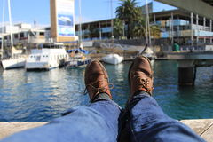 Sitting on the pier. Lying on the pier stretching legs and admiring the yachts in Barselona Royalty Free Stock Images