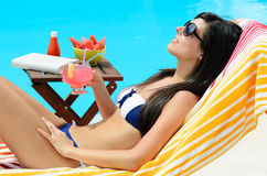 Lying by the Pool in Summer. Cheerful woman with drink and sunglasses . She is sunbathing and relaxing at the poolside with a book and fruit in a table Royalty Free Stock Images