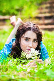 Lying pretty smiling girl in blue Royalty Free Stock Photos
