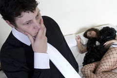 Lying prostitute. Man stressing about situation with prostitute on the bed behind him Stock Photos