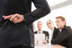 Lying?. Rear view of men in formalwear keeping fingers crossed behind his back while three people sitting on background Stock Photos